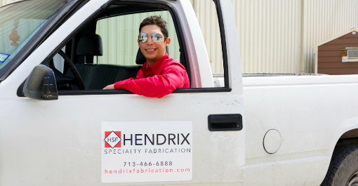 Hendrix Fabrication employee inside white truck.